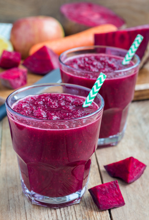 Healthy detox beetroot, carrot, apple and lemon juice smoothie in glass on wooden table, vertical Banco de Imagens