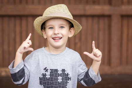 4 5 year old: Portrait of four years old boy in hat, playing cowboy, over brown wooden background Stock Photo
