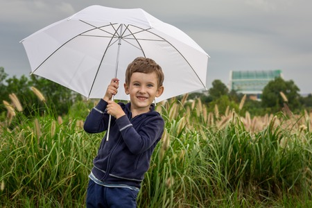 4 5 year old: Portrait outdoors of four five years old boy holding umbrella, horizontal