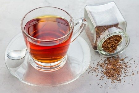 Cup of healthy herbal rooibos red tea in glass cup and dry tea on background Stock Photo