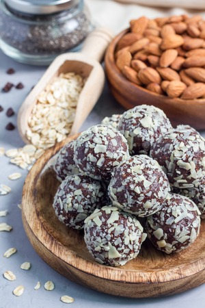 Healthy homemade paleo chocolate energy balls with rolled oats, nuts, dates and chia seeds, vertical