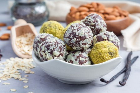 Healthy homemade paleo chocolate energy balls with rolled oats, nuts, dates and chia seeds, horizontal