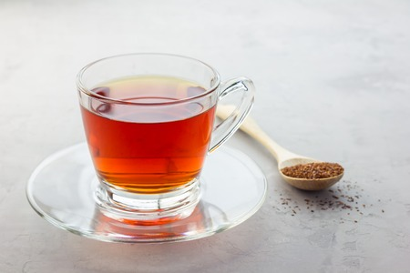 caffeine free: Cup of healthy herbal rooibos red tea in glass cup and dry tea on background, copy space