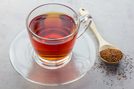 caffeine free: Cup of healthy herbal rooibos red tea in glass cup and dry tea on background Stock Photo