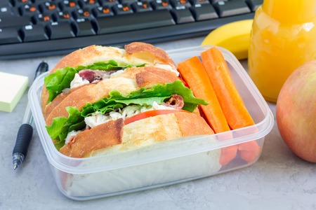 Lunch box with chicken salad sandwiches, served with carrot sticks. Fruits and juice on workplace background, horizontal
