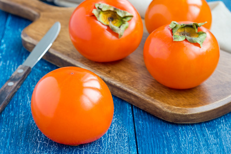 Cut persimmon fruits on wooden board and table, ready to eat, horizontal