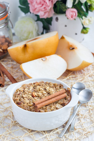 Baked oatmeal with nuts, almond milk, honey, spices and asian pear, vertical