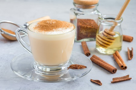 Healthy rooibos red tea latte topped with cinnamon, in glass cup and ingredients on background, horizontal