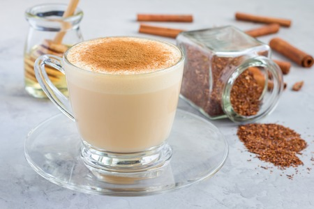 glass topped: Healthy rooibos red tea latte topped with cinnamon, in glass cup and ingredients on background, horizontal