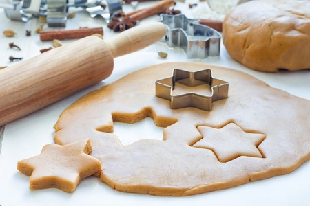 Making gingerbread cookies. Dough, metal cutter and rolling pen on wooden table, spices on background, horizontal