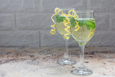 Spritzer cocktail with white wine, mint and ice, decorated with spiral lemon zest, horizontal, copy space