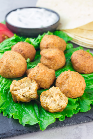 Chickpea falafel balls on slate board with vegetables and sauce, vertical