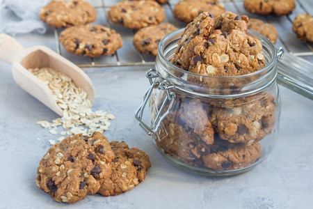 Flourless gluten free peanut butter, oatmeal and chocolate chips cookies in glass jar and on table, horizontal Standard-Bild