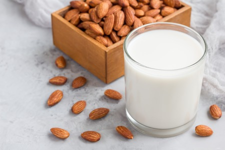 Almond milk in glass with almonds on background, horizontal, copy space Stock Photo