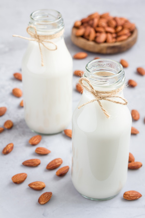 Almond milk in glass bottles with almonds on background, vertical