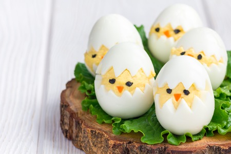 Little chicken in nest, deviled eggs served with salad on wooden board, horizontal, copy space