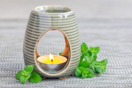 Pepermuntetherische olie in aromalamp op grijze mat met horizontale kuuroordachtergrond, exemplaarruimte