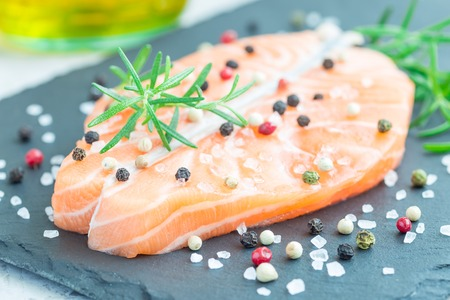 Fresh raw salmon steak with seasonings on stone board, horizontal Stock Photo