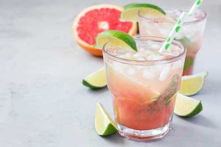 Cold pink cocktail with fresh grapefruit, lime and ice cubes on concrete background, paloma, copy space