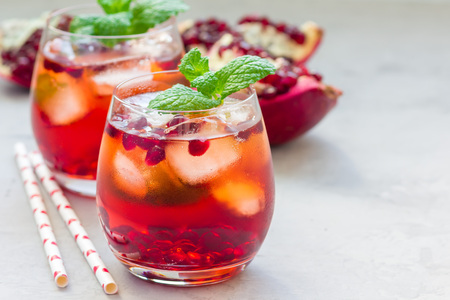 Mojito cocktail with pomegranate, mint, lemon juice and ice in glass, horizontal, copy space