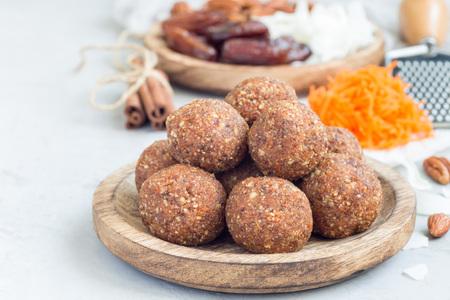 Gezonde eigengemaakte paleo energieballen met wortel, noten, data en kokosnotenvlokken, op houten horizontale plaat, exemplaarruimte Stockfoto