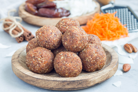 christmas grounds: Healthy homemade paleo energy balls with carrot, nuts, dates and coconut flakes, on wooden plate, horizontal