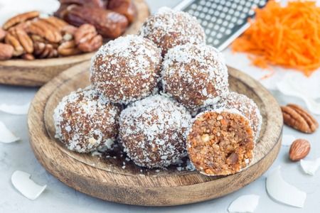 Healthy homemade paleo energy balls with carrot, nuts, dates and coconut flakes, horizontal
