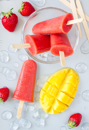 Homemade strawberry-mango popsicles on a gray background