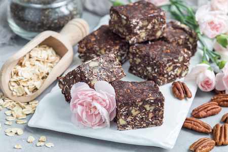 Paleo chocolate energy bars with rolled oats, pecan nuts, dates, chia seeds and coconut flakes, horizontal