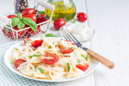 colourful tie: Pasta salad with tie pasta, feta cheese, cherry tomatoes, mustard and basil, copy space, horizontal Stock Photo