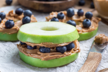 Healthy sandwich. Green apple rounds with peanut butter and and blueberries on wooden table, horizontal Archivio Fotografico