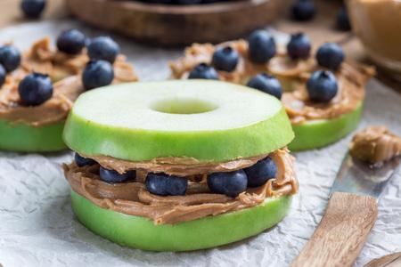 Panino sano. Mezzi di mele verdi con burro di arachidi e mirtilli sul tavolo di legno, orizzontale Archivio Fotografico - 82585873