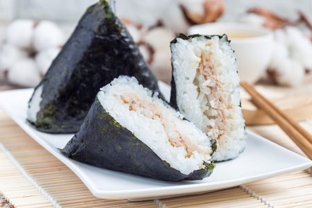 El kimbap Samagak coreano del triángulo hizo con nori, el arroz y el atún, similar al onigiri japonés de la bola de arroz. Horizontal Foto de archivo - 83988340