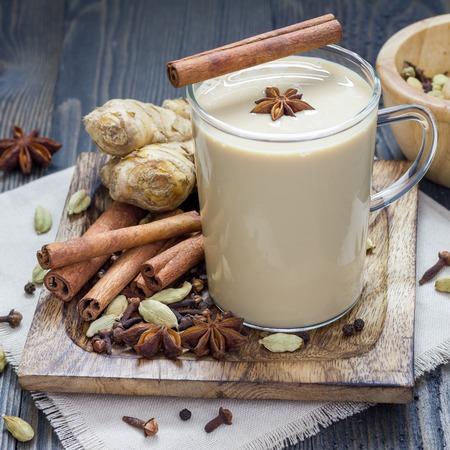 Masala-chai met kruiden op een houten achtergrond. Kaneelstokje, kardemom, gember, kruidnagel, steranijs, zwarte peper, vierkant formaat Stockfoto