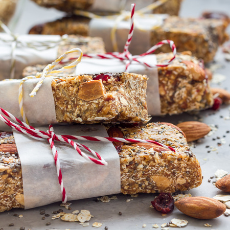 Homemade granola energy bars with figs, oatmeal, almond, dry cranberry, chia and sunflower seeds, square format
