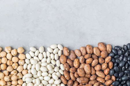 Different kinds of beans: black, pinto, white and chickpeas, on concrete background, copy space, horizontal Stock Photo