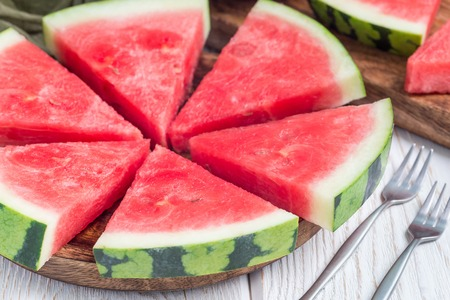 Slices of fresh seedless watermelon cut into triangle shape on a wooden plate, horizontal