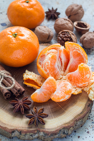 yule log: Christmas background. Aromatic winter spices, walnuts and mandarins laying on a wooden log, vertical Stock Photo