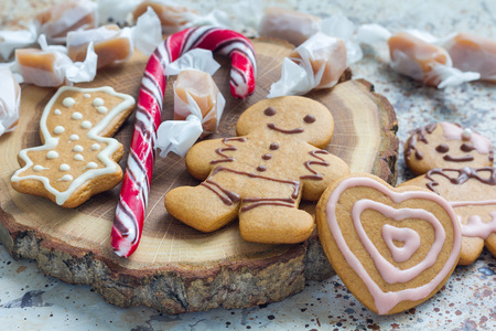 Sweet gifts for holiydays. Homemade christmas gingerbread cookies and caramel candies on a wooden board, horizontal Stock Photo
