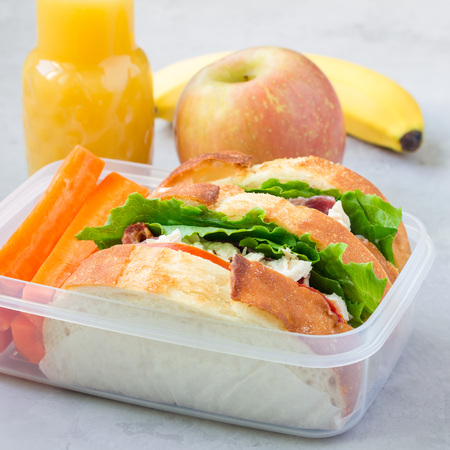 Lunch box with chicken salad sandwiches, served with carrot sticks. Fruits and juice on background, square format