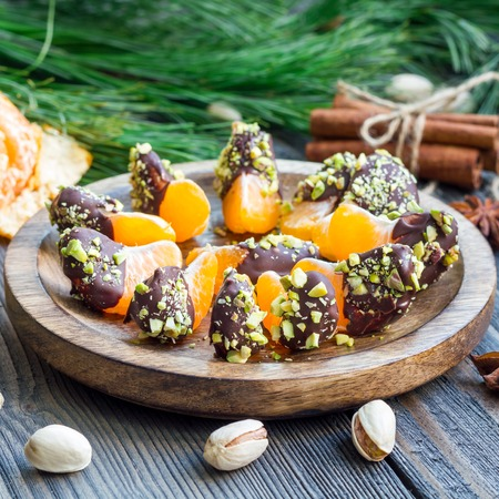 Mandarins covered with chocolate and pistachio, square format Standard-Bild