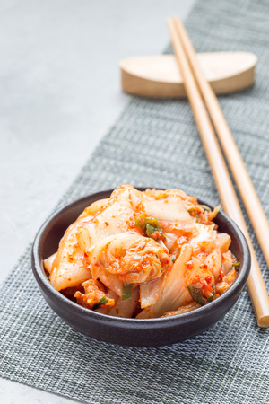 Kimchi cabbage. Korean appetizer in a ceramic bowl, vertical, copy space