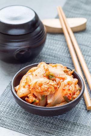 Kimchi cabbage. Korean appetizer in a ceramic bowl, vertical