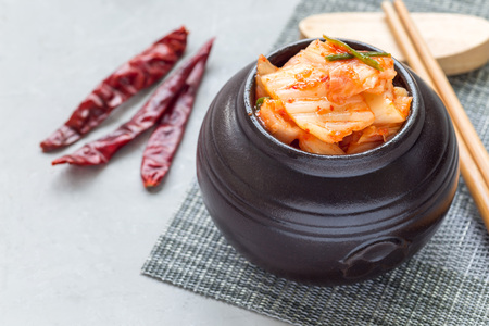 korean salad: Kimchi cabbage. Korean appetizer in a ceramic jar, horizontal Stock Photo
