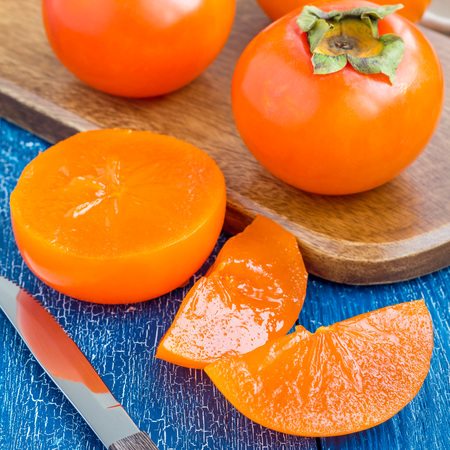 Cut persimmon fruits on wooden board and table, ready to eat, square format