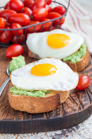Open sandwiches with mashed avocado and fried egg on toasted bread, vertical Standard-Bild