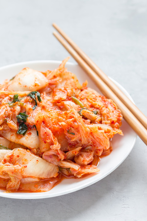 Kimchi cabbage. Korean appetizer on a white plate, vertical