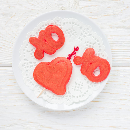Red velvet pancakes with xo sign, hugs and kisses, and heart on white plate, top view, square format