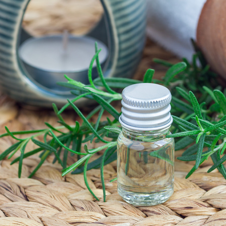 Rosemary essential oil in glass on woven mat with spa background, square format