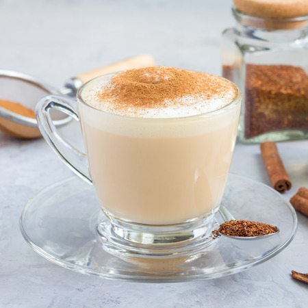 Healthy rooibos red tea latte topped with cinnamon, in a glass cup and ingredients on background, square